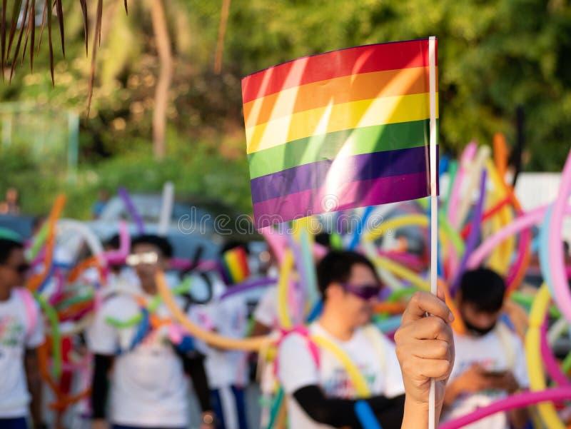 Fundo do mês do orgulho de LGBT um espectador acena uma bandeira alegre do arco-íris no festival da parada de orgulho alegre de L foto de stock royalty free