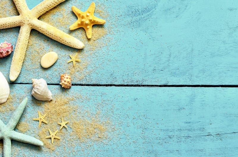 Fundo do mar do verão Estrela do mar, conchas do mar e areia em um fundo azul de madeira fotografia de stock royalty free