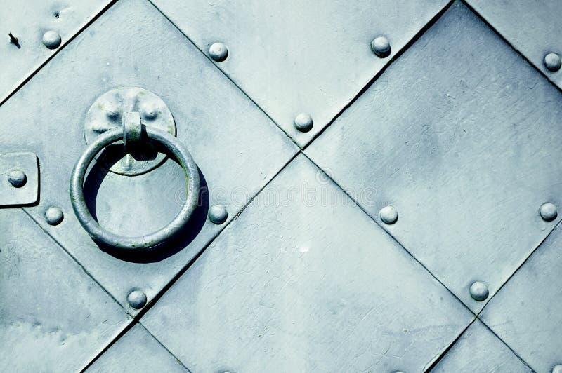 Fundo do metal do vintage - porta cinzenta velha com rebites e o puxador da porta envelhecido do metal sob a forma do anel imagem de stock