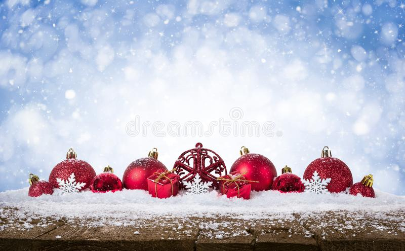 Fundo do Natal - as bolas vermelhas decoradas na neve com snowflakesand stars na mesa de madeira fotos de stock