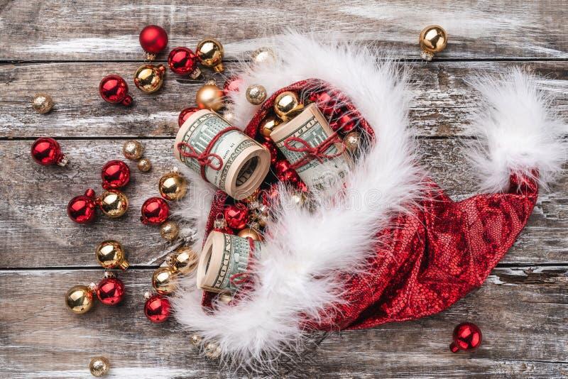 Fundo do Natal, chapéu de Santa Claus completamente das quinquilharias e dinheiro de madeira velhos Vista superior imagem de stock
