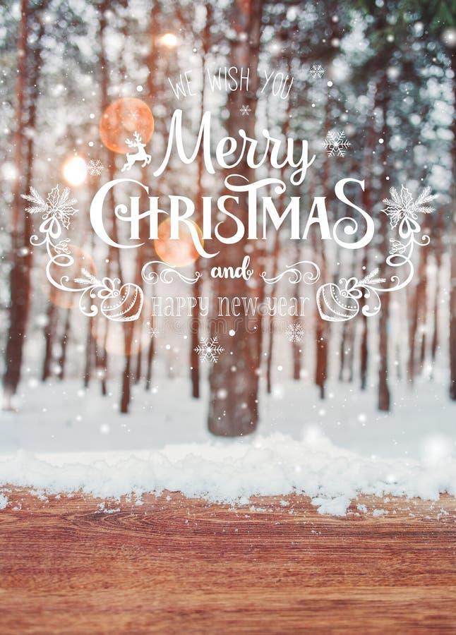 Fundo do Natal com abeto e fundo borrado do inverno com Feliz Natal do texto e a tabela nova feliz do ano e a de madeira fotos de stock
