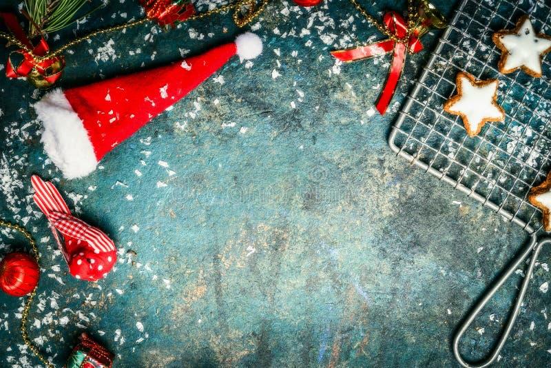 Fundo do Natal com chapéu de Santa, neve, a decoração vermelha do inverno e as cookies da estrela, vista superior foto de stock royalty free