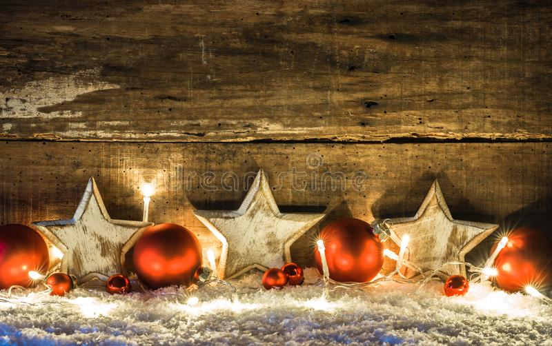 Fundo do Natal com estrelas brancas, as quinquilharias vermelhas e as luzes sobre a neve na noite imagens de stock