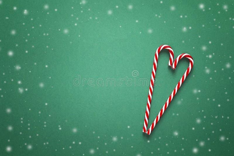 Fundo do Natal com os bastões de doces vermelhos na forma do coração imagens de stock
