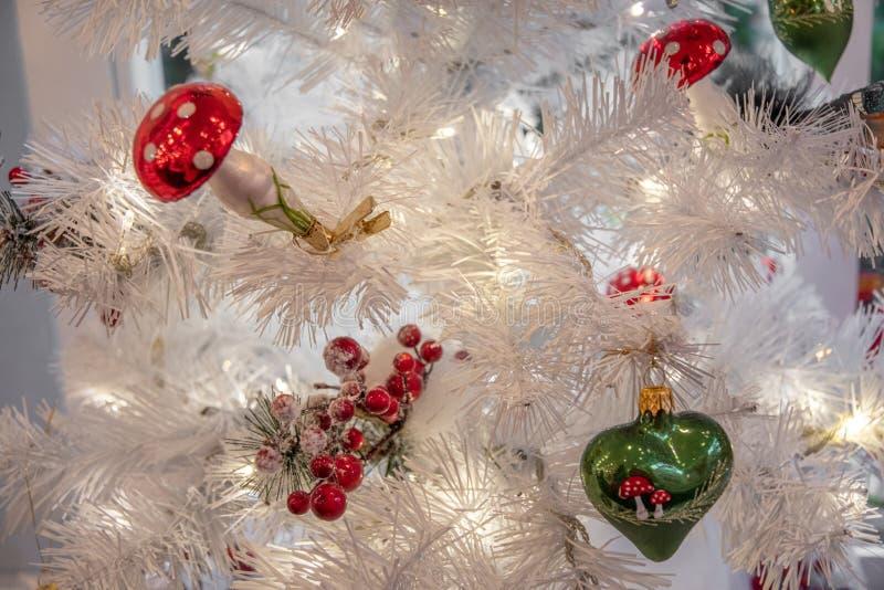 Fundo do Natal com ramos artificiais brancos do abeto, os ornamento de vidro mornos de brilho das luzes de Natal, os vermelhos e  imagens de stock royalty free