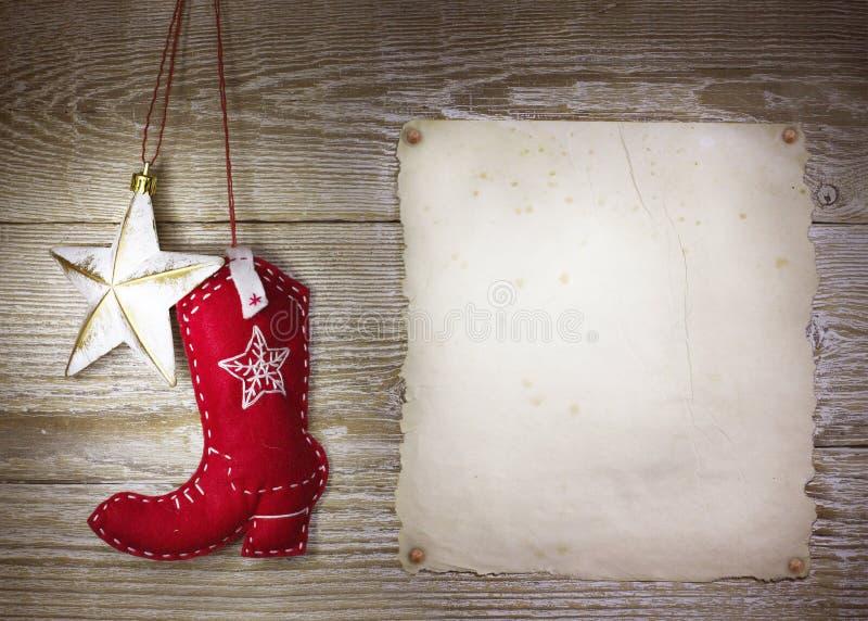Fundo do Natal do vaqueiro com a bota ocidental dos brinquedos e estrela no foto de stock