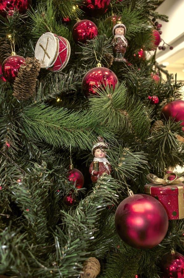 Fundo do Natal dos ramos naturais e artificiais do pinho com as decorações do Natal, os cilindros, as estatuetas, os cones do pin imagem de stock