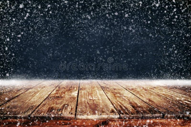 Fundo do Natal e do ano novo com a tabela e queda de neve de madeira da plataforma fotografia de stock