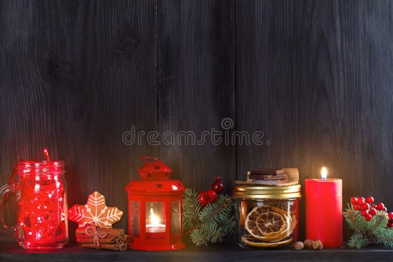 Fundo do Natal e do ano novo com vela, luz, decorações e caixa de presente na prateleira de madeira imagens de stock royalty free