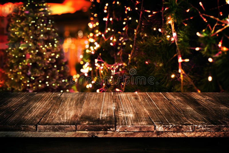 Fundo do Natal e do ano novo com a tabela de madeira escura vazia da plataforma sobre a árvore de Natal e o bokeh claro borrado imagem de stock royalty free