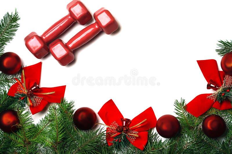 Fundo do Natal do esporte e do ano novo com pesos vermelhos, as bolas de vidro vermelhas verdes de árvore de abeto dos ramos e os imagens de stock royalty free