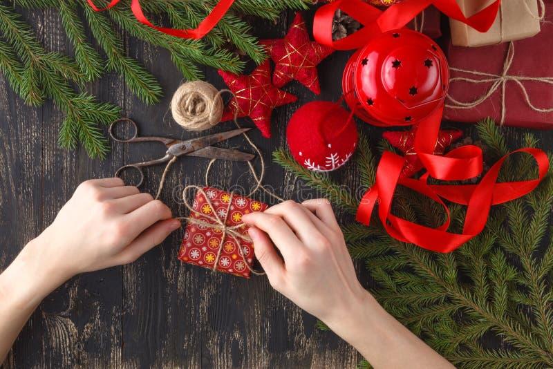 Fundo do Natal A ideia superior das mãos da criança envolve o presente do ano novo Presentes e rolos embalados, ramos spruce e fe imagem de stock royalty free