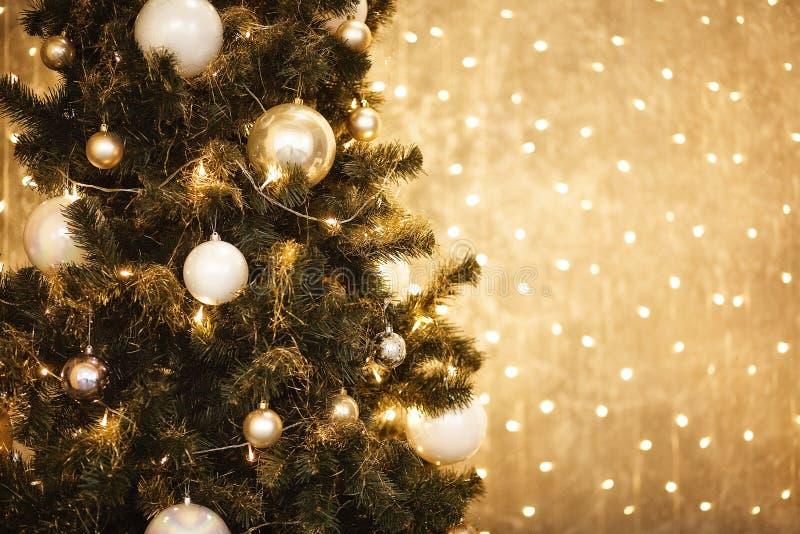 Fundo do Natal do ouro de luzes de-focalizadas com árvore decorada 2018 fotos de stock royalty free