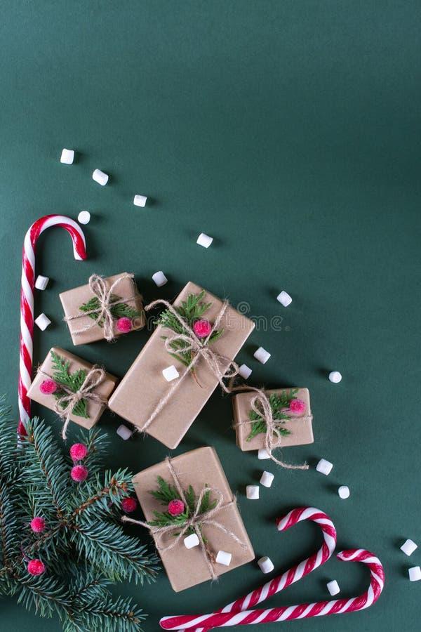 Fundo do Natal Presentes da embalagem no papel bege do ofício do vintage e na decoração natural Ramos do abeto e da baga vermelha fotografia de stock