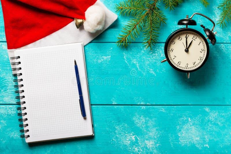 Fundo do Natal Ramos do abeto, chapéu de Santa Claus, despertador do vintage e caderno com uma pena no fundo de madeira azul c?pi fotografia de stock