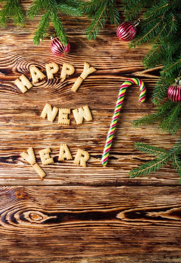 Fundo do Natal Ramos do abeto, bolas vermelhas, cookies e bastões de doces na placa marrom idosa Estilo rústico Copie o espaço imagem de stock royalty free