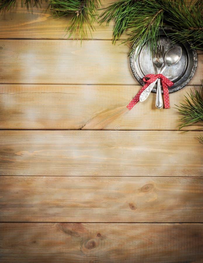 Fundo do Natal Tabela, ramo do pinho e artigos de madeira antigos do vintage Bandeja, forquilha de prata e colher, amarradas com  foto de stock royalty free