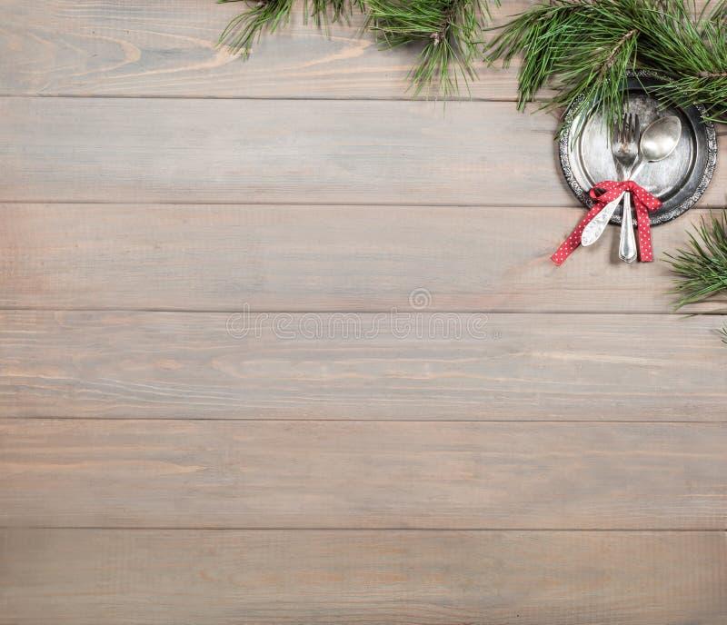 Fundo do Natal Tabela, ramo do pinho e artigos de madeira antigos do vintage Bandeja, forquilha de prata e colher, amarradas com  fotografia de stock royalty free