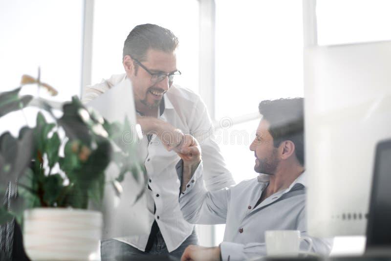 Fundo do negócio Dois colegas masculinos de sorriso que dão colisões do punho fotos de stock royalty free