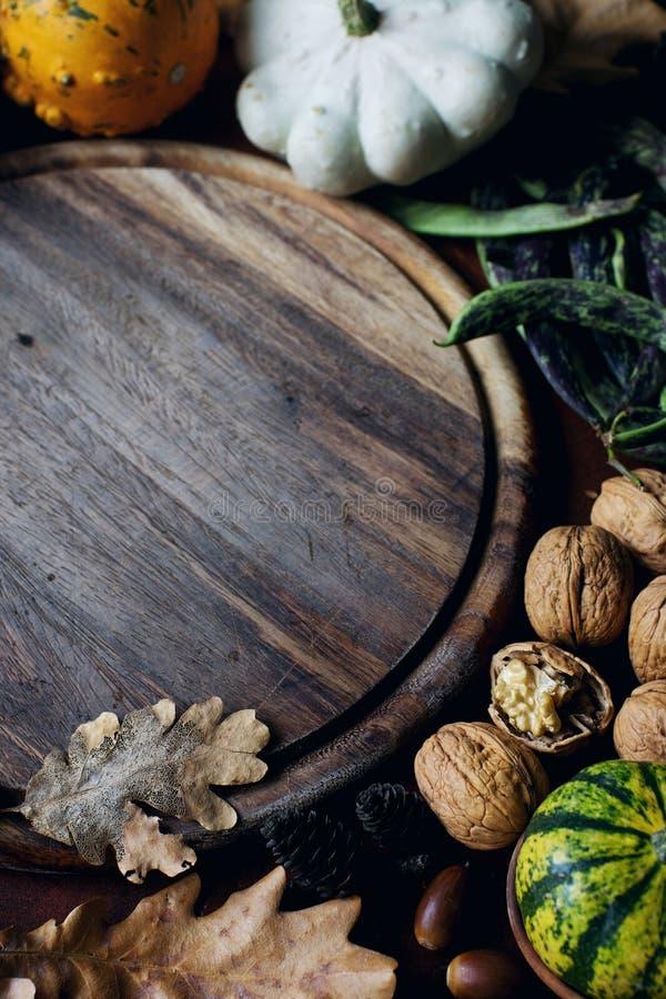 Fundo do outono com abóbora decorativa, bolotas, porcas, verdes, folhas de outono e placa de madeira com espaço para o texto na p imagens de stock