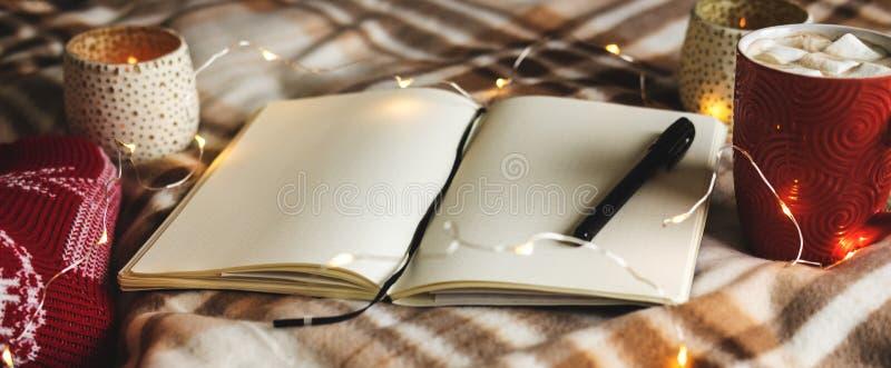 Fundo do outono e do inverno com caderno, pena, festão, velas, pés do ` s da mulher nas peúgas vermelhas feitas malha, caneca de  fotografia de stock royalty free