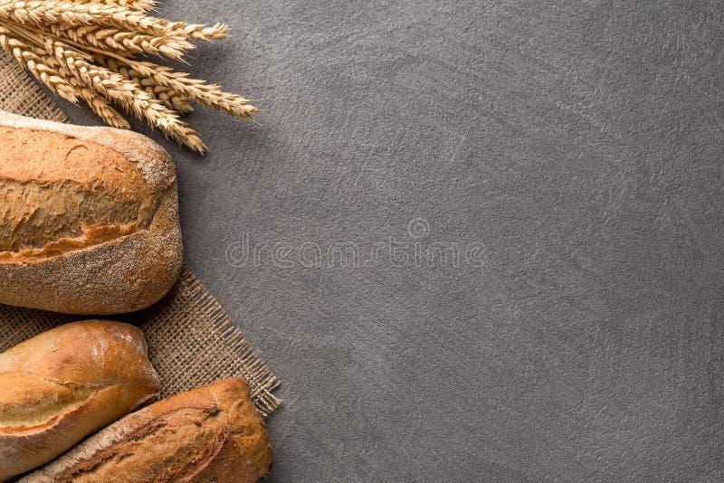 Fundo do pão com trigo, pão estaladiço aromático com grões, espaço da cópia Vista superior imagem de stock