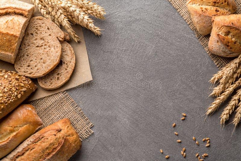 Fundo do pão com trigo, pão estaladiço aromático com grões, espaço da cópia, vista superior Brown e da grão dos nacos vida inteir fotos de stock