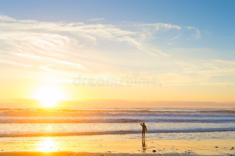Fundo do por do sol da praia do oceano do surfista fotografia de stock