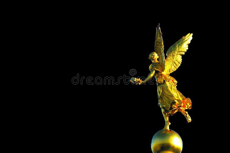 Fundo do preto da estátua do anjo do ouro fotos de stock royalty free