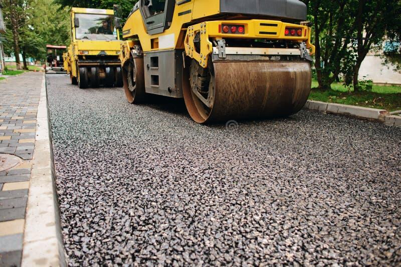 Fundo do rolo do asfalto que empilha e pressiona o asfalto quente Máquina do reparo da estrada foto de stock royalty free