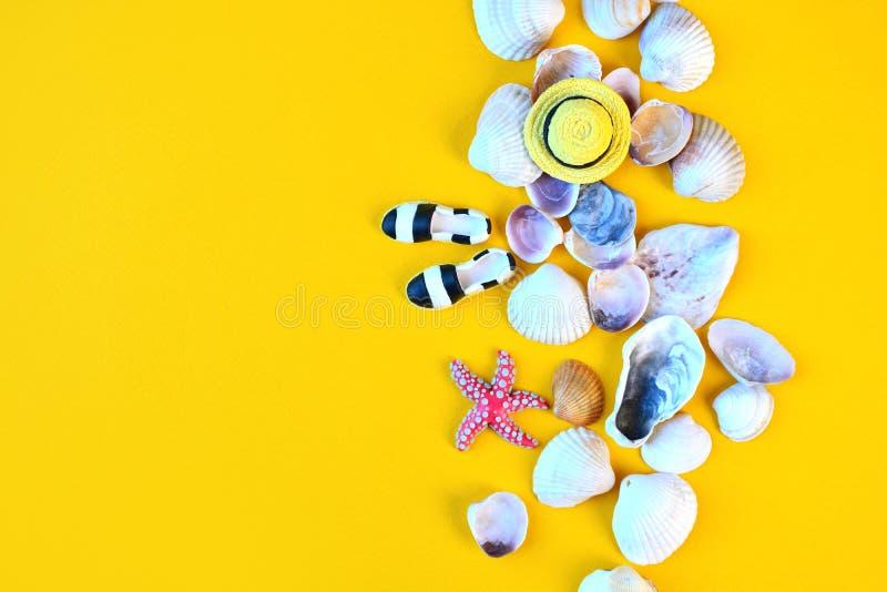 Fundo do verão Acessórios colocados lisos da praia do viajante no fundo amarelo com conchas do mar, o chapéu diminuto e os mocass fotos de stock royalty free