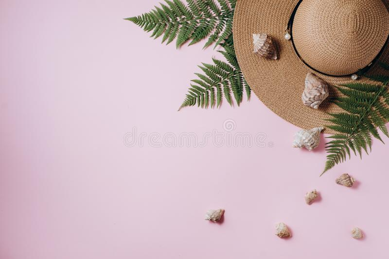 Fundo do ver?o Acessórios do viajante, ramos tropicais da folha da samambaia, chapéu e concha do mar no fundo cor-de-rosa Conceit foto de stock