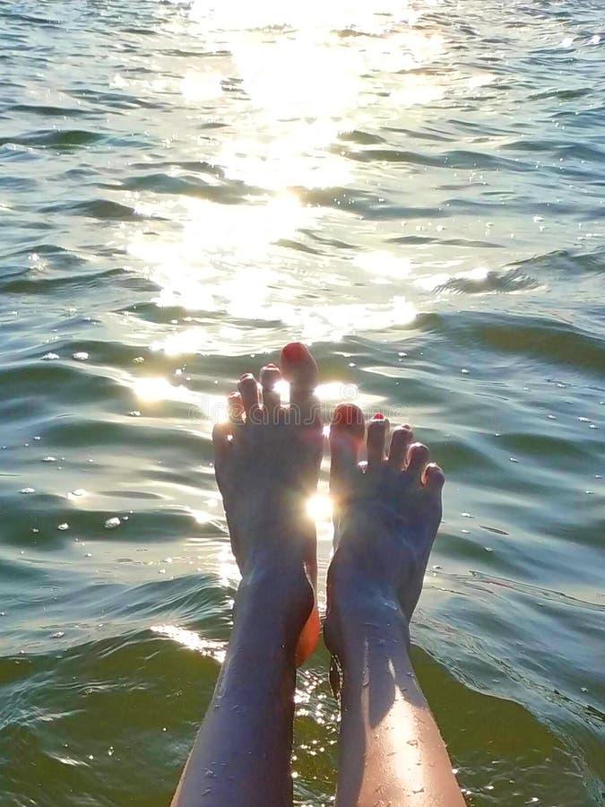 Fundo do ver?o Pés fêmeas no mar contra o fundo da reflexão da luz solar na água fotos de stock royalty free