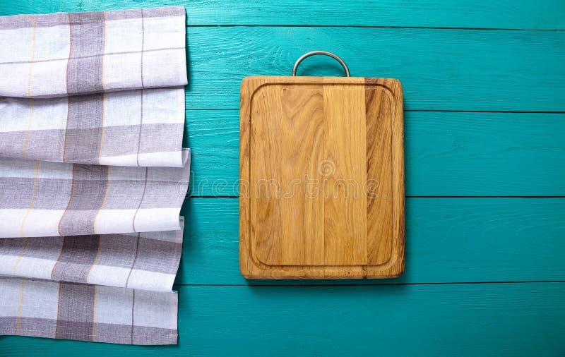 Fundo do vintage Toalha de mesa da placa e da manta de corte na tabela de madeira azul Vista superior e zombaria acima conceito d imagens de stock