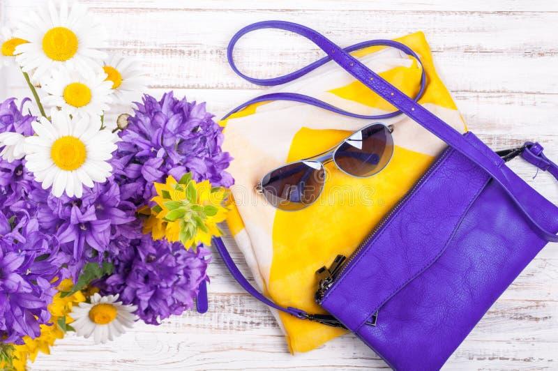 Fundo dos acessórios da mulher com bolsas, lenço de pescoço, óculos de sol e flores Os equipamentos da mulher do verão imagens de stock