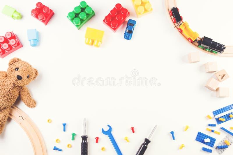Fundo dos brinquedos das crianças com blocos e cubos da construção, ferramentas dos brinquedos, trem de madeira e urso de peluche foto de stock