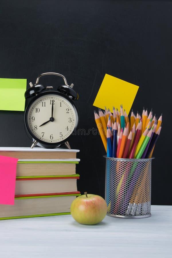 Fundo dos grupos de artigos do escritório e um despertador preto em livros coloridos, ao lado de um vidro com lápis imagem de stock