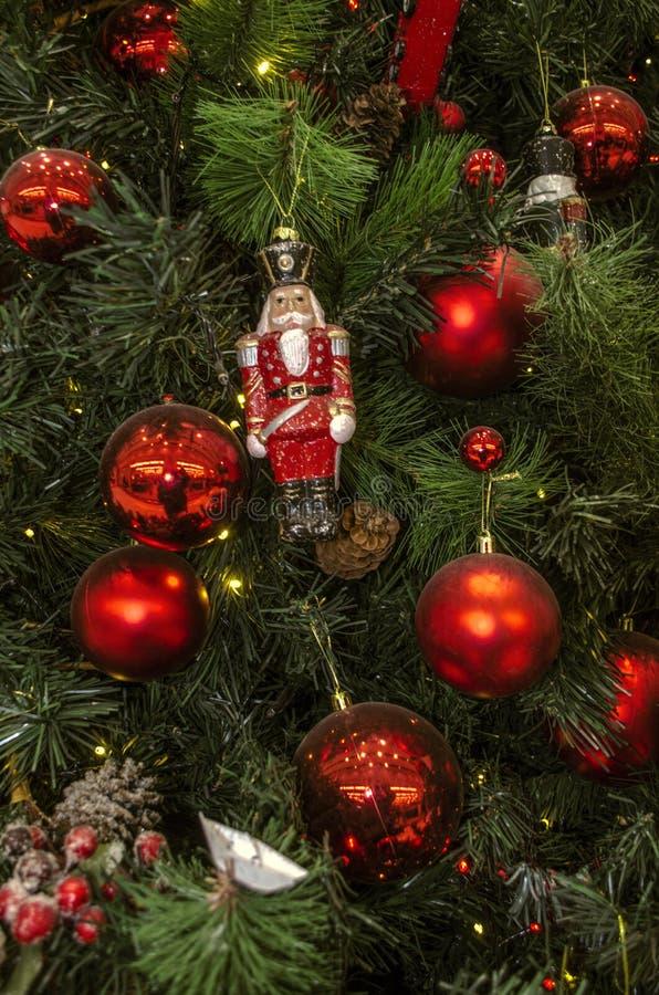 Fundo dos ramos naturais e artificiais do pinho com um brinquedo velho da quebra-nozes, umas estatuetas, uns cones e umas bolas v foto de stock royalty free