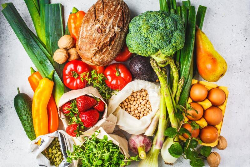 Fundo equilibrado do alimento Vegetais, frutos, porcas, brotos, ovos, sementes, grãos-de-bico no fundo branco, vista superior fotografia de stock