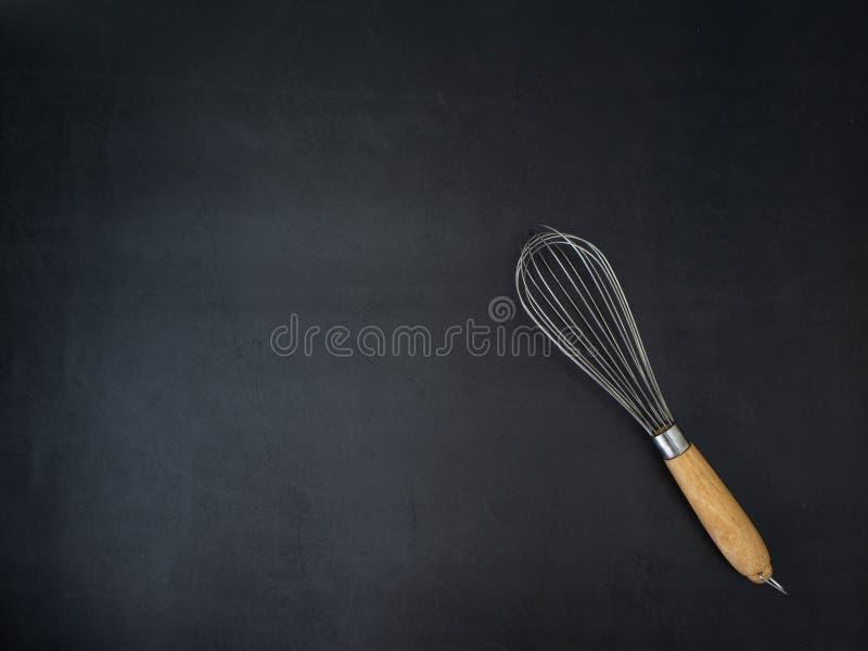 Fundo escuro da placa do granito do batedor de ovos do fio foto de stock royalty free