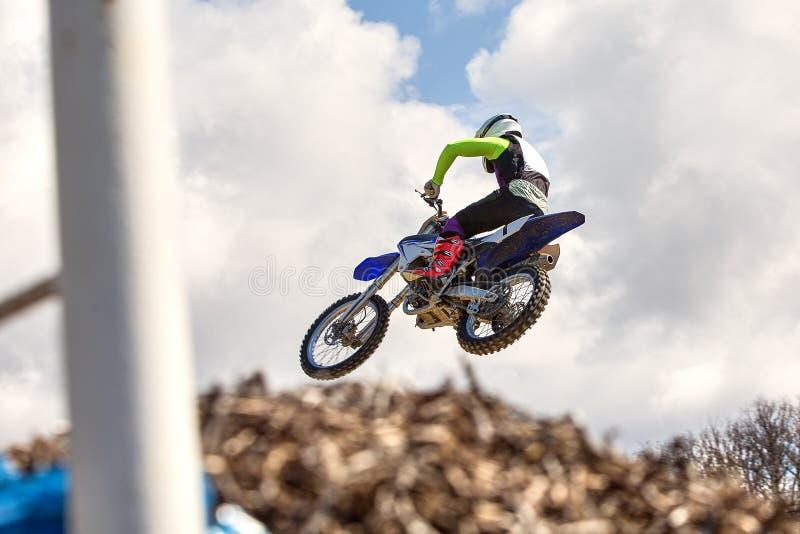 Fundo extremo dos esportes - silhueta do motociclista que salta no velomotor no por do sol, contra o céu azul com nuvens imagem de stock royalty free