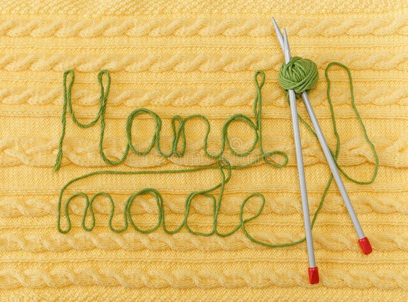 Fundo feito malha amarelo com teste padrão e tranças; Grey Knitting Needle e bola verde Feito à mão; Bordado Sinal feito à mão fotografia de stock royalty free