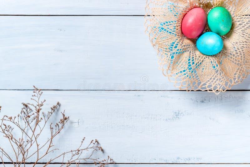 Fundo feliz da beira de easter, quadro de ovos da páscoa coloridos na cesta e ramo de flores secadas imagens de stock royalty free
