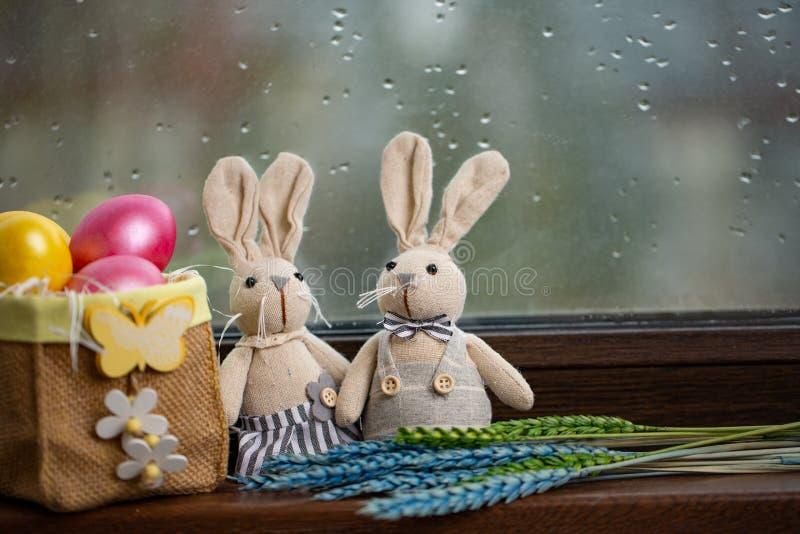 Fundo feliz da P?scoa com os ovos coloridos na cesta e na lebre Tabela que decora para o feriado fotografia de stock