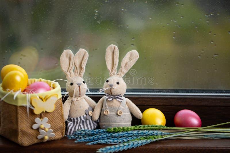 Fundo feliz da P?scoa com os ovos coloridos na cesta e na lebre Tabela que decora para o feriado foto de stock
