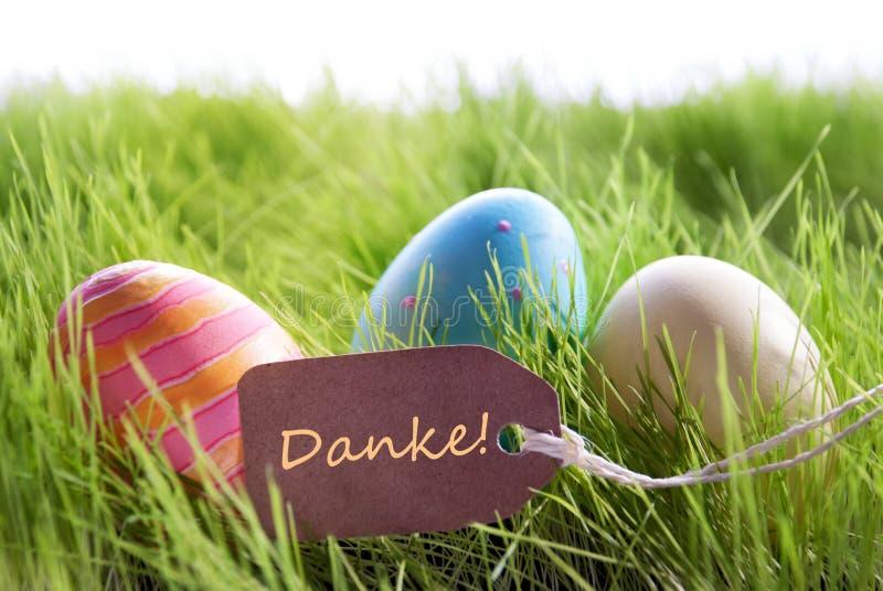 Fundo feliz da Páscoa com ovos coloridos e etiqueta com texto alemão Danke fotos de stock