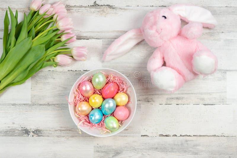 Fundo feliz da Páscoa com ovos, tulipas e o coelho enchido imagens de stock