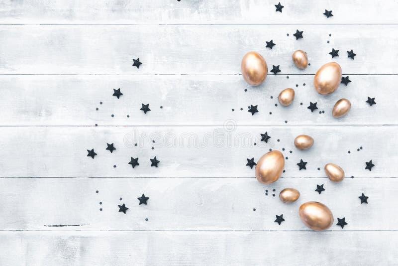Fundo feliz de easter Composição lisa da configuração com ovos do ouro e as estrelas pretas imagens de stock