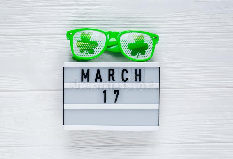 Fundo festivo criativo do St Patricks com vidros verdes caixa leve calendário do 17 de março branco e do divertimento com trevo fotografia de stock